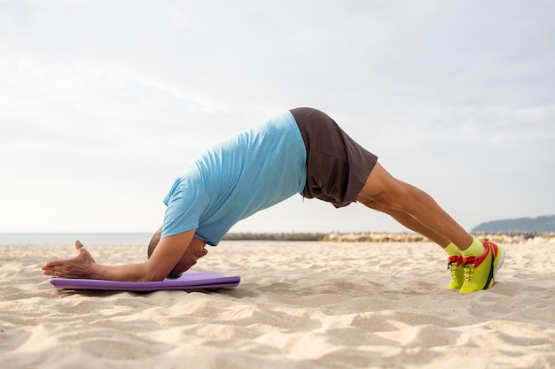 Vista lateral de um homem mais velho fazendo exercícios na praia