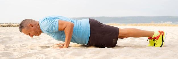 Vista lateral de um homem mais velho malhando na praia