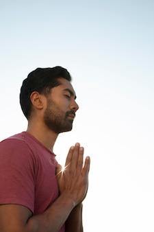 Vista lateral de um homem meditando ao ar livre
