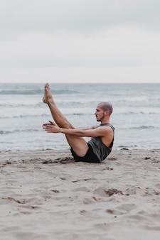 Vista lateral de um homem na praia em posição de ioga com espaço de cópia