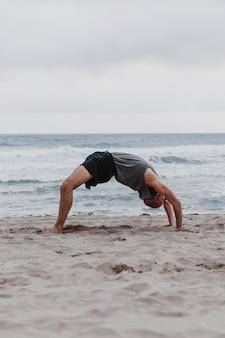 Vista lateral de um homem na praia em posição de ioga