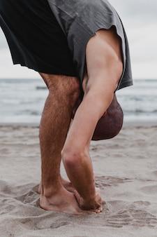 Vista lateral de um homem na praia fazendo posições de ioga na areia