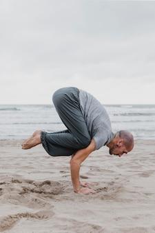 Vista lateral de um homem na praia praticando ioga