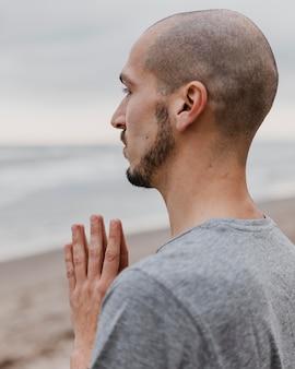 Vista lateral de um homem na praia praticando meditação de ioga