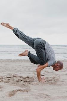 Vista lateral de um homem na praia praticando posições de ioga