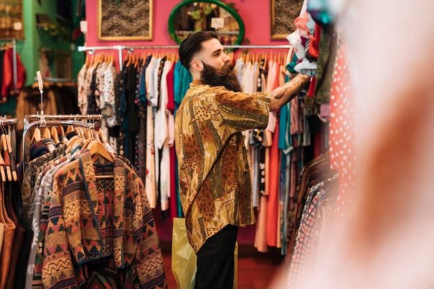 Vista lateral, de, um, homem olha, em, roupas, pendurar, a, trilho, em, a, loja