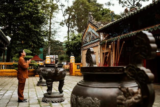 Vista lateral de um homem orando no templo com incenso