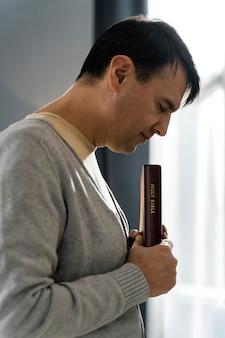 Vista lateral de um homem piedoso segurando a bíblia