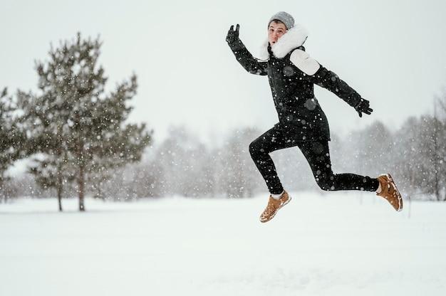 Vista lateral de um homem pulando no ar ao ar livre no inverno