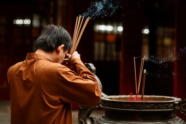 Vista lateral de um homem religioso no templo com incenso e espaço de cópia
