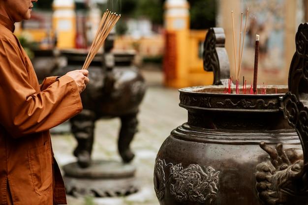Vista lateral de um homem religioso no templo com incenso queimando