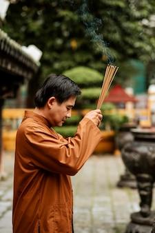 Vista lateral de um homem religioso no templo com incenso