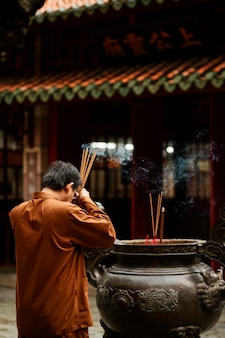 Vista lateral de um homem religioso no templo queimando incenso e copiando espaço