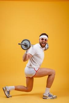 Vista lateral de um homem retrô fitness fazendo agachamentos com barra