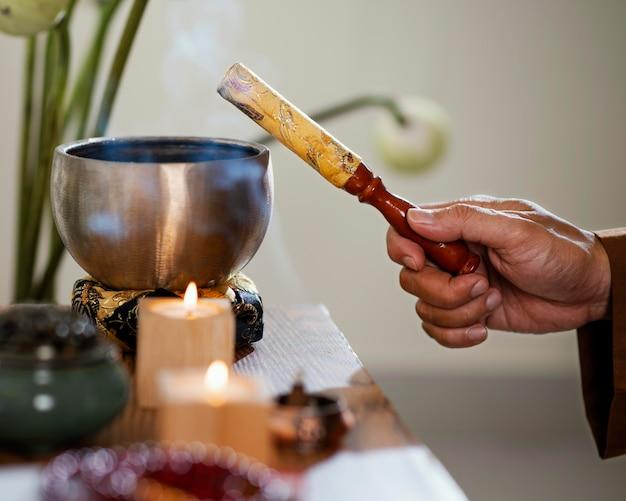 Vista lateral de um homem segurando um objeto para oração com velas e tigela