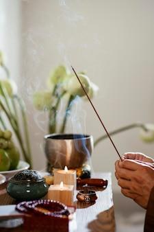 Vista lateral de um homem segurando um palito de incenso