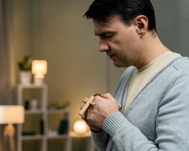 Vista lateral de um homem segurando uma cruz de madeira e orando