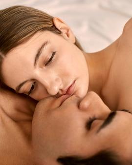 Vista lateral de um homem sem camisa e uma mulher na cama