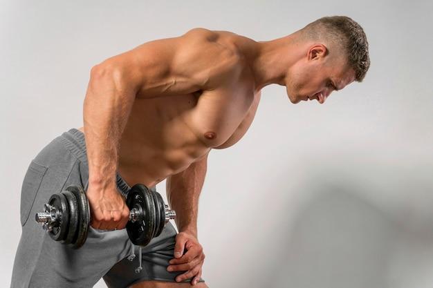 Vista lateral de um homem sem camisa malhando com peso