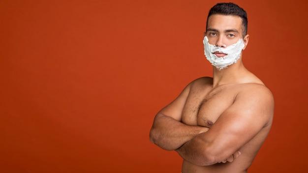 Vista lateral de um homem sem camisa posando com creme de barbear no rosto