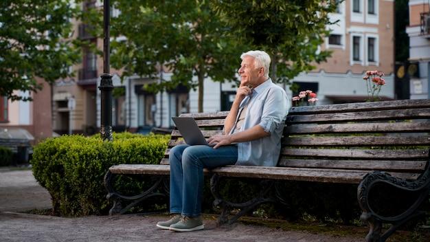 Vista lateral de um homem sênior ao ar livre em um banco com um laptop