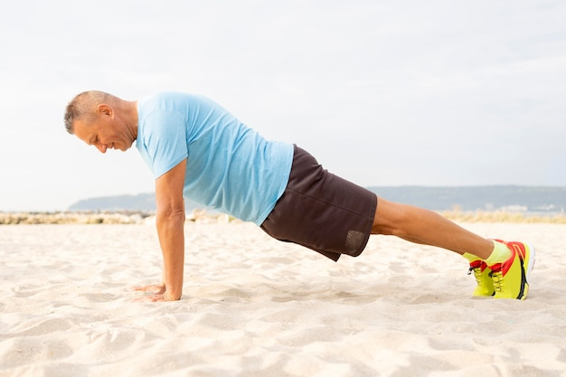 Vista lateral de um homem sênior fazendo exercícios na praia