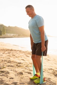 Vista lateral de um homem sênior malhando com uma corda elástica na praia