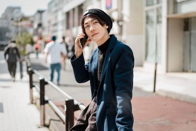 Vista lateral de um homem sentado na grade e falando ao telefone