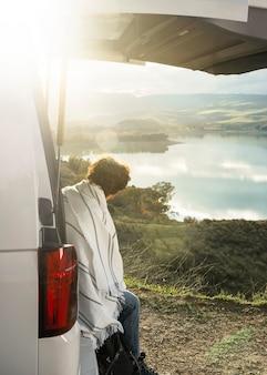 Vista lateral de um homem sentado no porta-malas do carro durante uma viagem