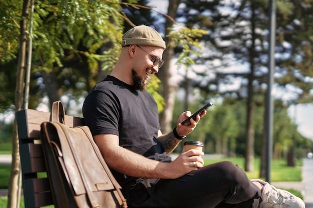 Vista lateral de um homem sorridente com roupas casuais, sente-se no banco enquanto navega em um smartphone ao ar livre na rua