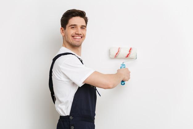 Vista lateral de um homem sorridente, pintando a parede com um rolo de dor sobre a parede cinza