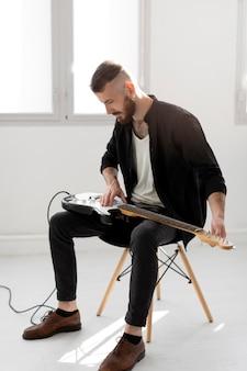 Vista lateral de um homem tocando guitarra elétrica