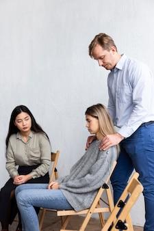 Vista lateral de um homem tocando o ombro de uma mulher em uma sessão de terapia de grupo