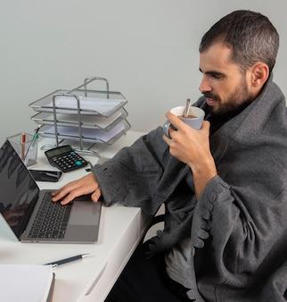 Vista lateral de um homem tomando café enquanto trabalha em casa