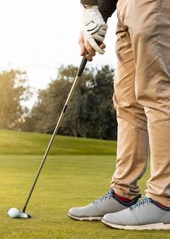 Vista lateral de um homem usando o taco para acertar a bola de golfe