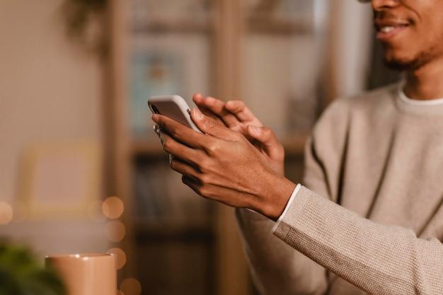 Vista lateral de um homem usando seu smartphone em casa