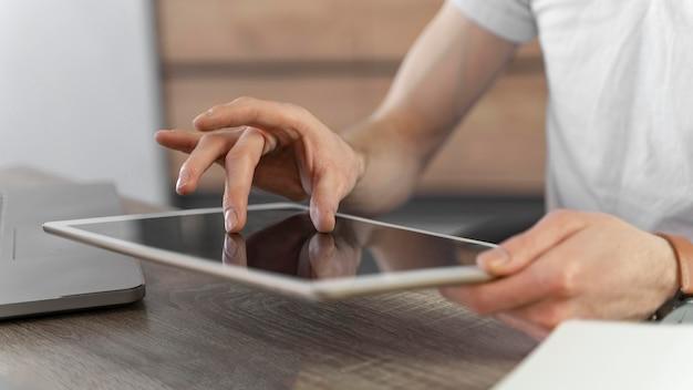 Vista lateral de um homem usando um tablet