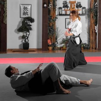 Vista lateral de um instrutor de artes marciais e estagiária na sala de prática