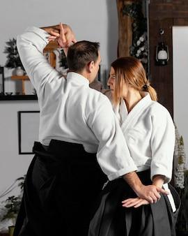 Vista lateral de um instrutor de artes marciais e estagiária praticando juntos