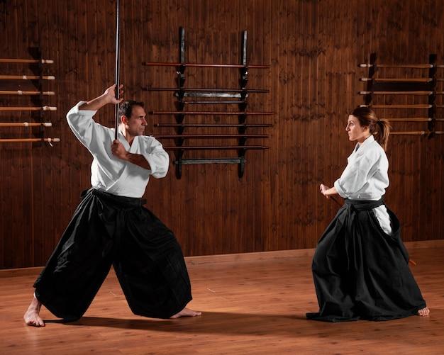 Vista lateral de um instrutor de artes marciais na sala de prática com uma estagiária