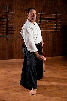 Vista lateral de um instrutor de artes marciais na sala de prática com uma vara de madeira