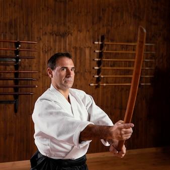 Vista lateral de um instrutor de artes marciais na sala de prática
