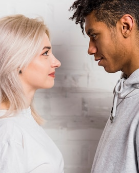 Vista lateral, de, um, interracial, par, amigo, olhando um ao outro