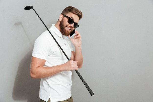 Vista lateral de um jogador de golfe calmo em óculos de sol, falando pelo smartphone e segurando o taco na mão sobre parede cinza
