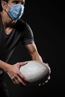 Vista lateral de um jogador de rúgbi com máscara médica segurando uma bola