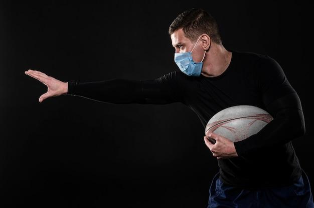 Vista lateral de um jogador de rugby com máscara médica e bola