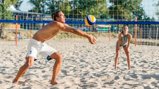 Vista lateral de um jogador de vôlei jogando na praia