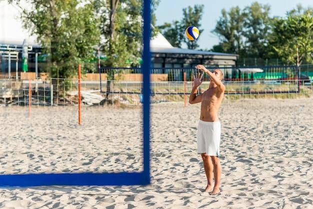 Vista lateral de um jogador de vôlei masculino sem camisa treinando com bola na praia