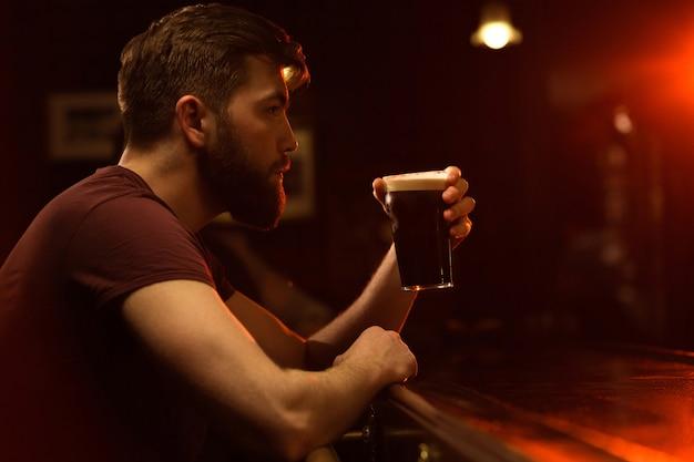Vista lateral de um jovem bebendo copo de cerveja