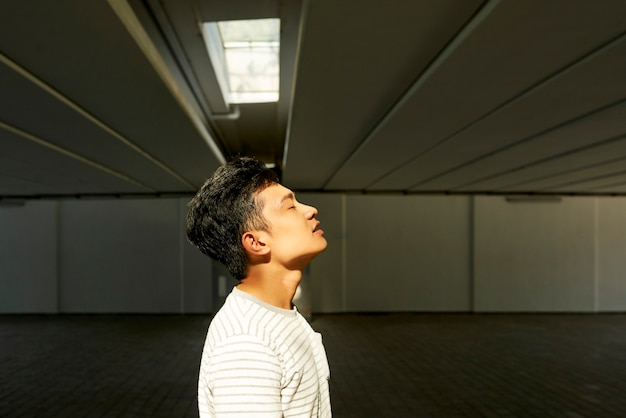 Vista lateral de um jovem bonito respirando fundo, preparando-se para a filmagem no estacionamento subterrâneo